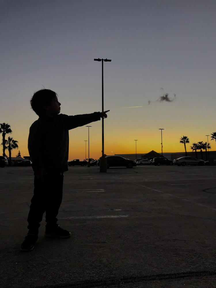 Little boy silhouette pointing at airplane during a sunset