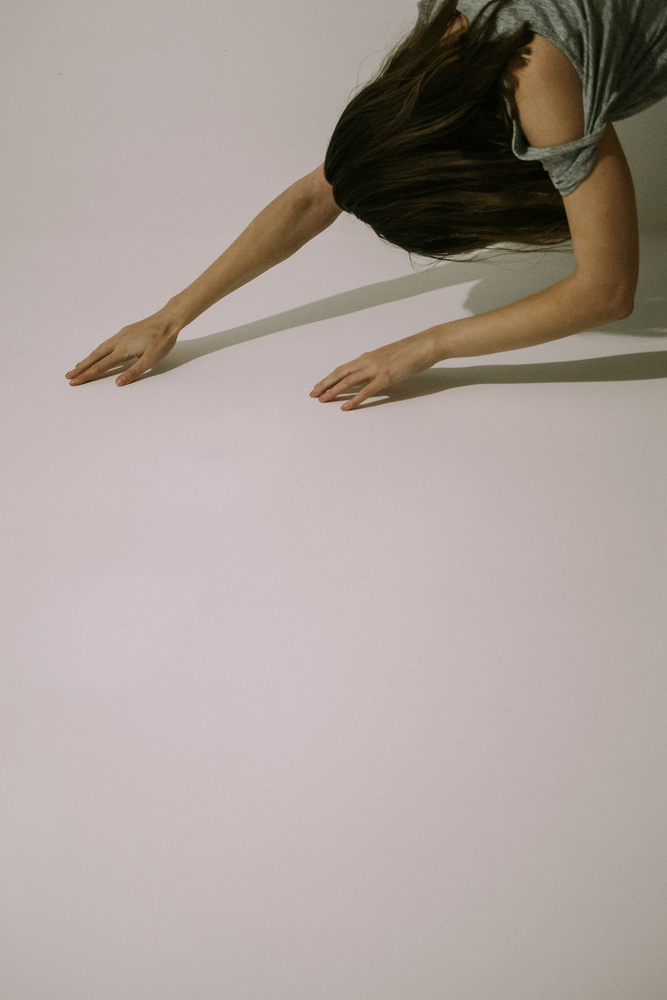 A woman holding hands up to a white wall