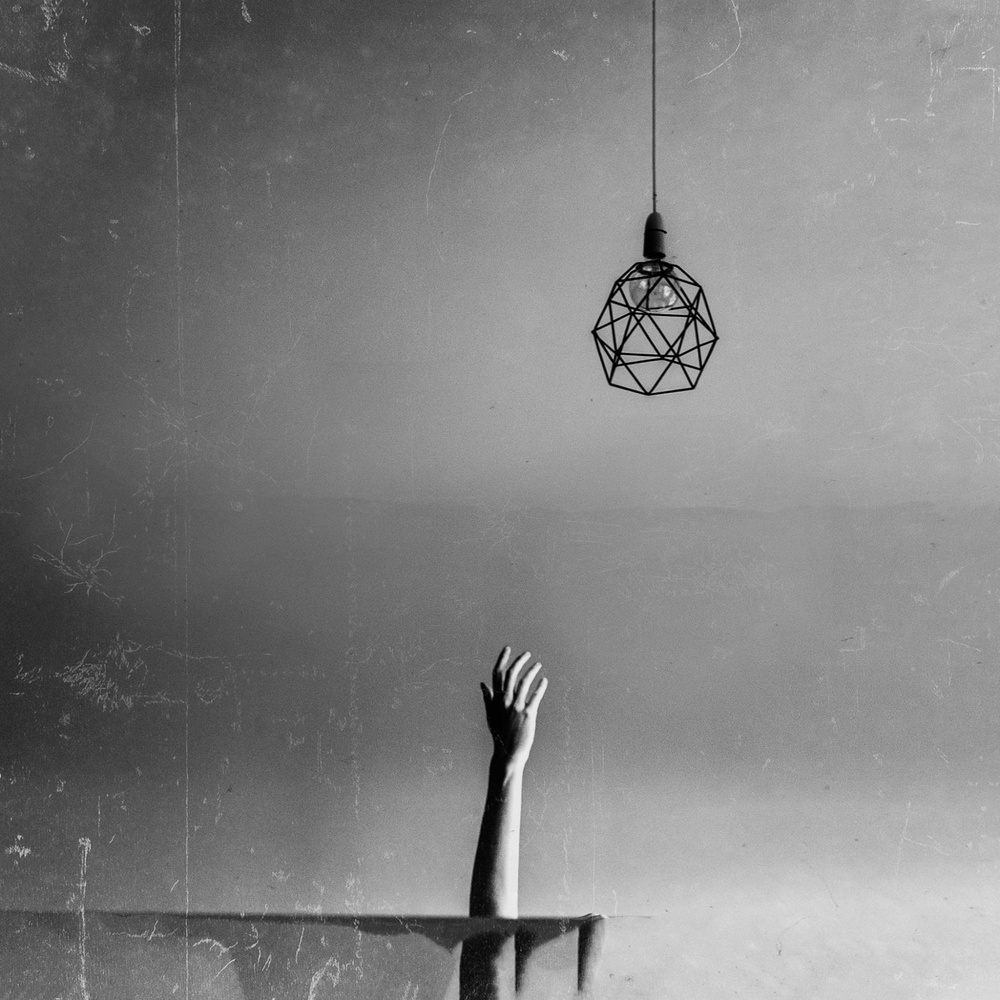 A hand reaching up towards the ceiling light.