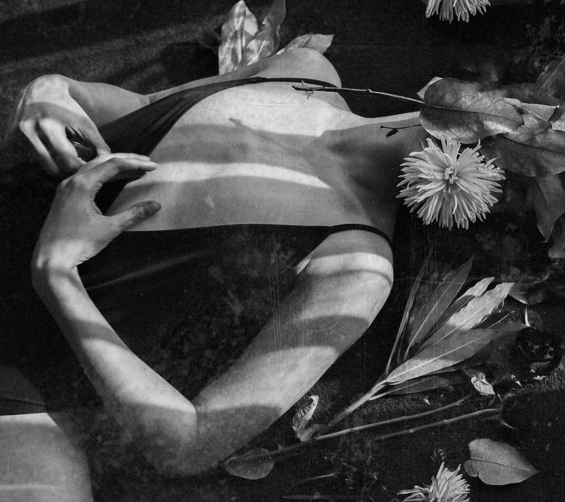 A girl's body covered with plants and flowers.