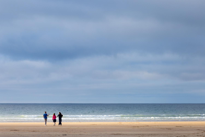Three people walk on a sandy beach towards the horizon above the sea.