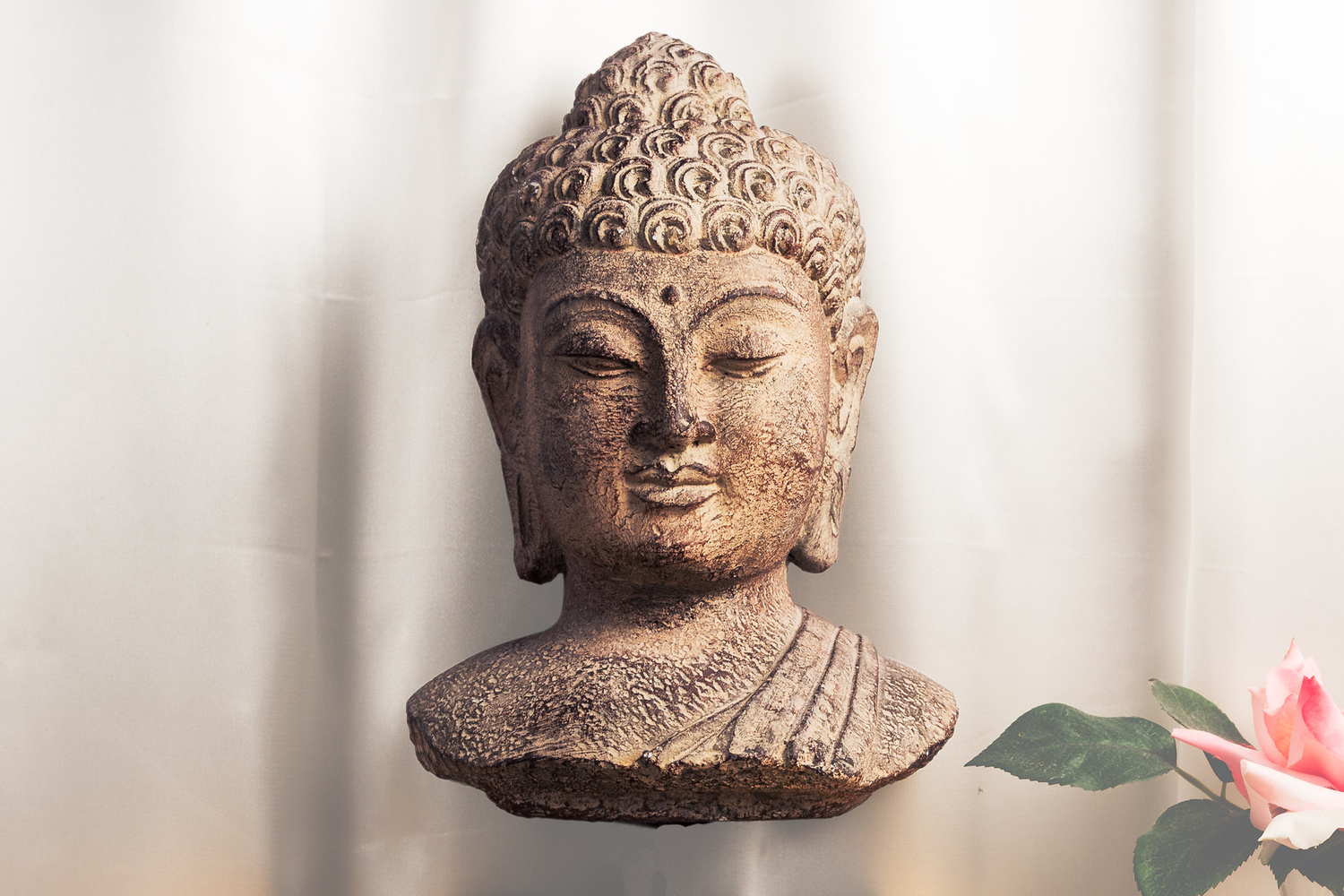A floating bust of the Buddha in front of a silk curtain with a pink flower and green leaves.