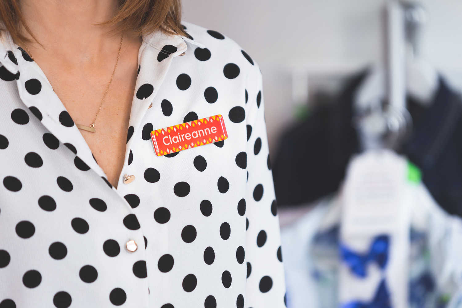 A retail employee wearing a black polka-dot blouse with a name tag
