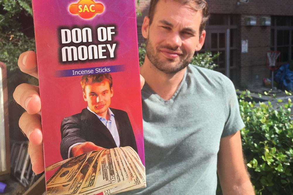 Lee Morris of Fstopper holding a leaflet with a photo of himself holding some twenty dollar bills.