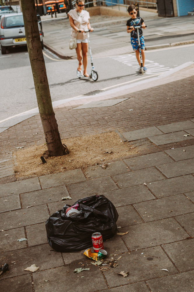 A rubbish bag laying on the street with people walking by