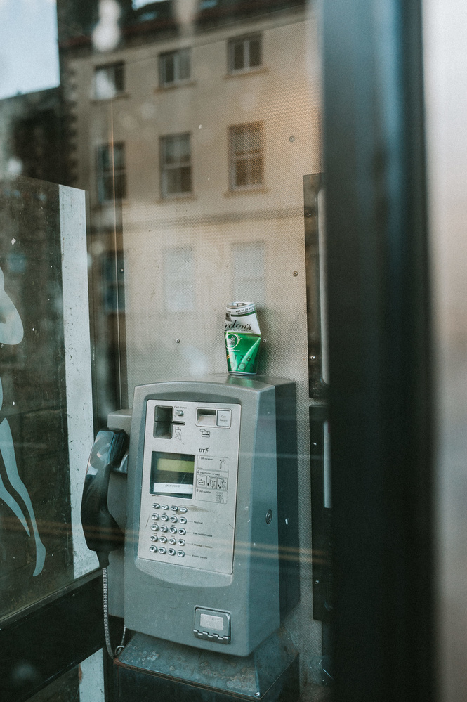 An used beer can on top of a pay phone