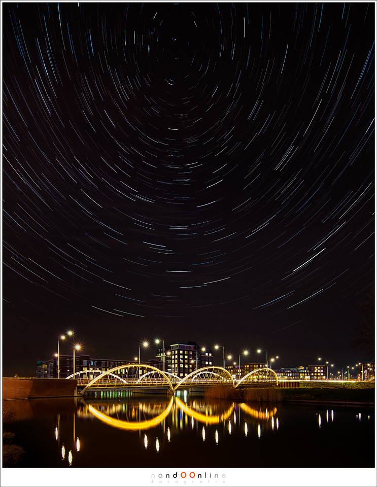 It is easy to shoot star trails in the middle of the city, if the settings are correct. This is composed from 329 individual shots, each 8 seconds at ISO3200 and f/8, and a seperate foreground shot. (EOS 5D mark III + TS-E 17mm | ISO3200 | f/4 | 329x 8 se