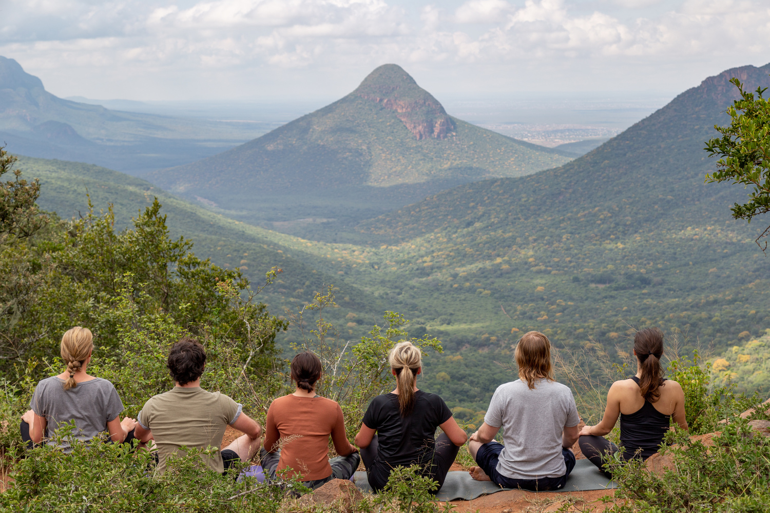 group of people sit meditating overlooking a beautiful vista with a valley and mountains.