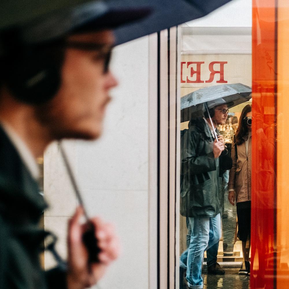 A man with an umbrella walking past a photographer.