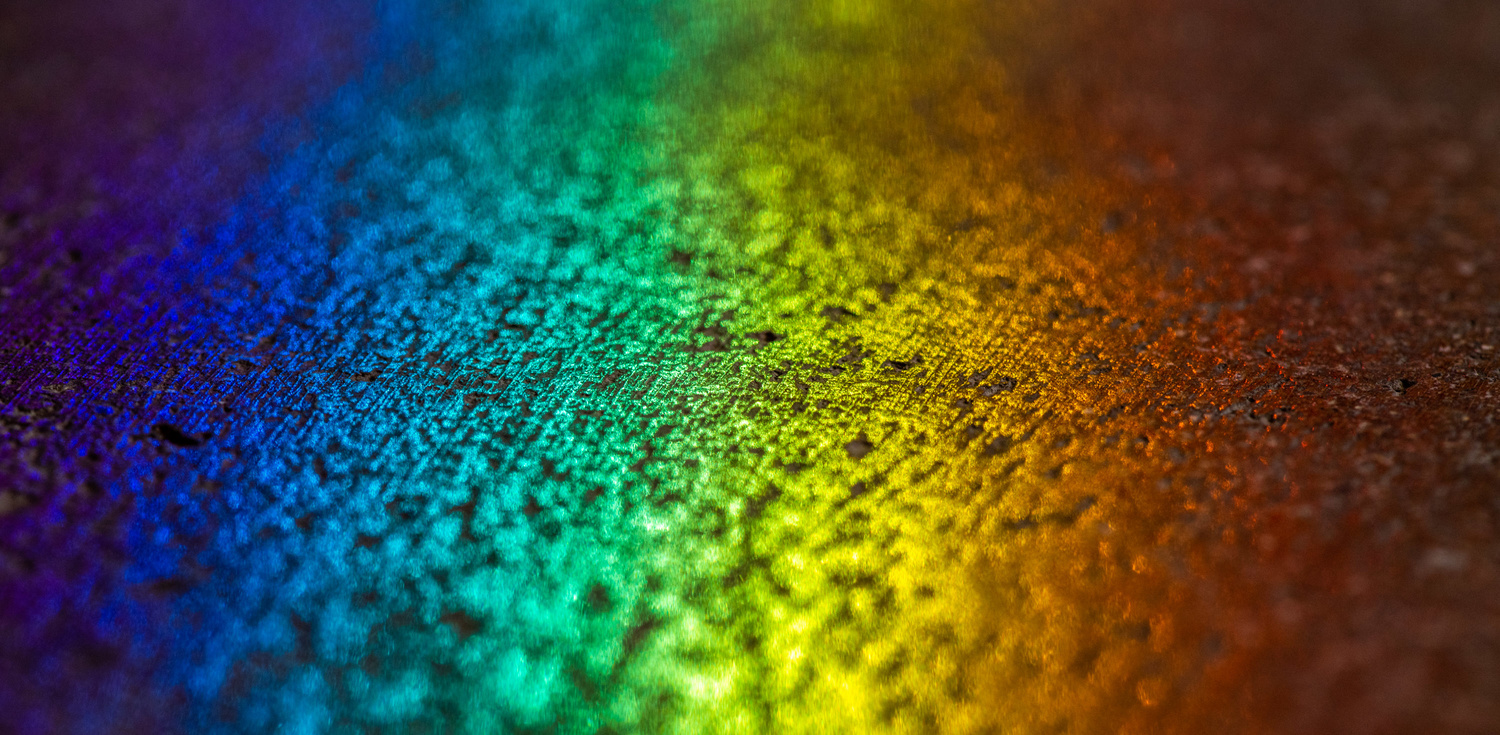 a macro photo showing a rainbow reflection on a surface close-up