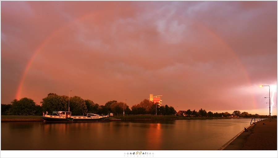 A red sky during sunset, with a rainbow that is almost completely red. This is called a redbow. A keen eye will spot also lightning at the right side of this shot. (Canon EOS 5D3 with 17mm | ISO200 | f/13 | 4 sec)