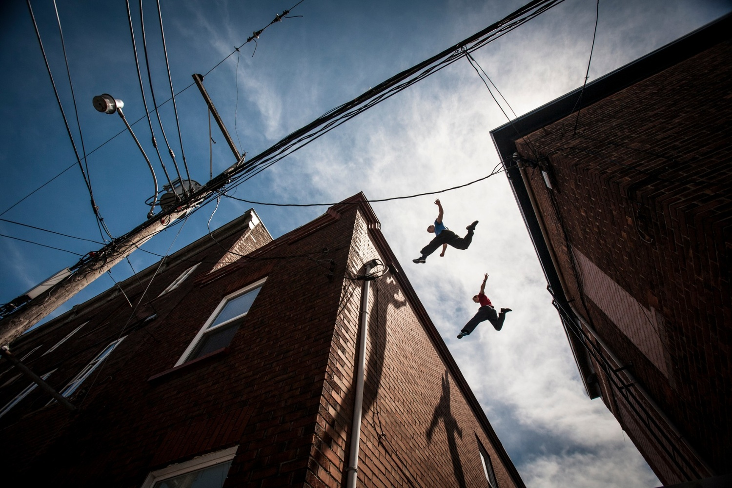 professional sports photography of parkour athletes jumping over rooftops