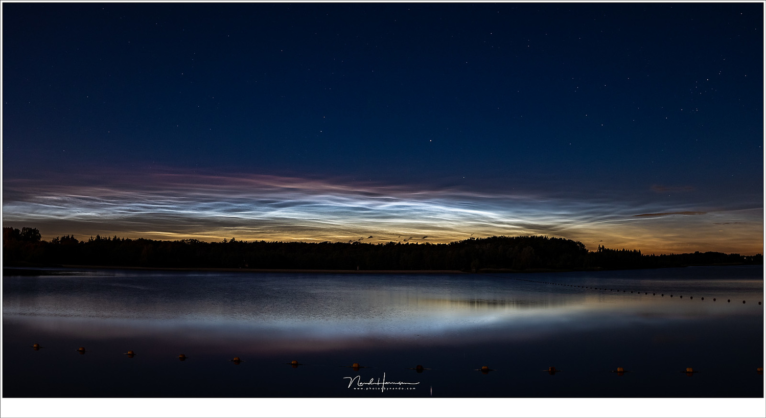 A clear panoramic view at a nearby swimming lake. Twilight colors show at the bottom, and the red glow of the noctilucent clouds appears at the top.  Stars are visible through the clouds and in the night sky. (Lumix DC-S1 + 49mm | ISO1600 | f/5,6 | 4 sec)
