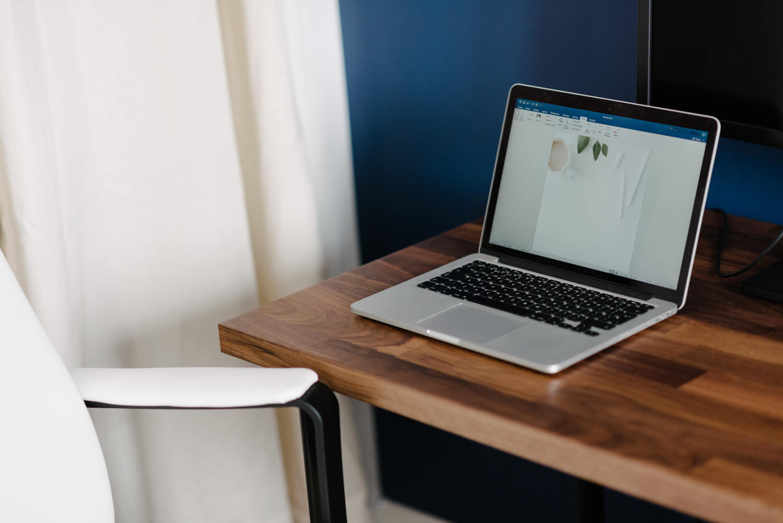 A laptop on a wooden desk.