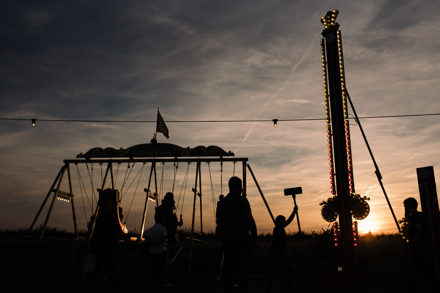 Children playing at a fairground during sunset.