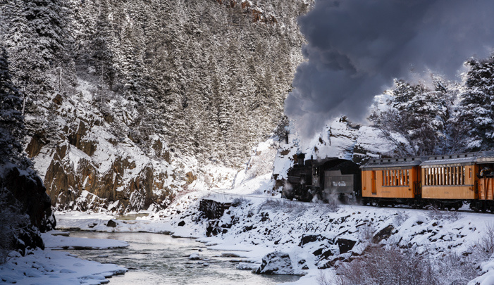 Photograph of a steam train traveling along mountain river in the snow.
