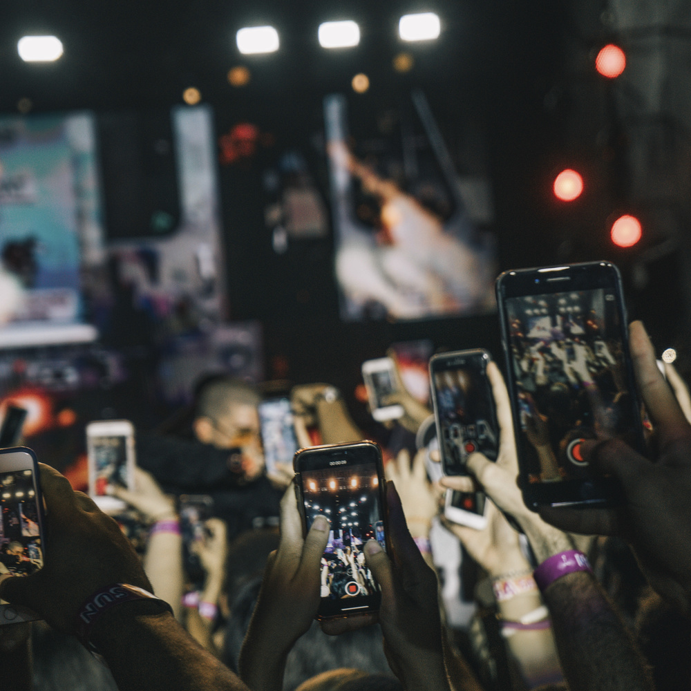 people holding up their smart phones at a concert