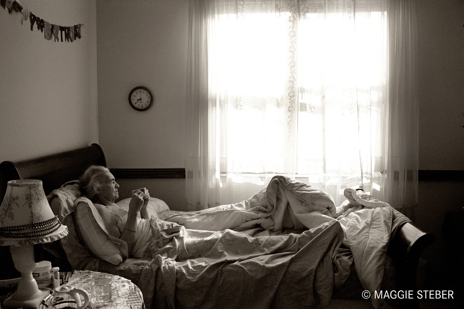 An older woman having a cup of drink in bed.