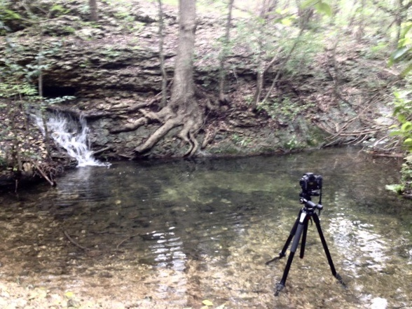 a photo showing a camera and tripod in water taking a waterfall picture