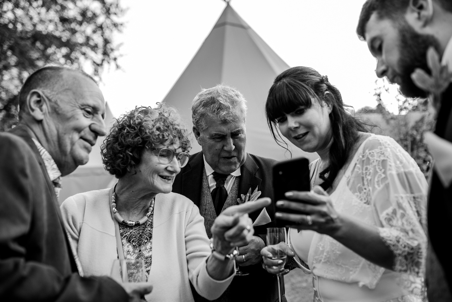 Wedding guests and the bride and groom looking at a phone