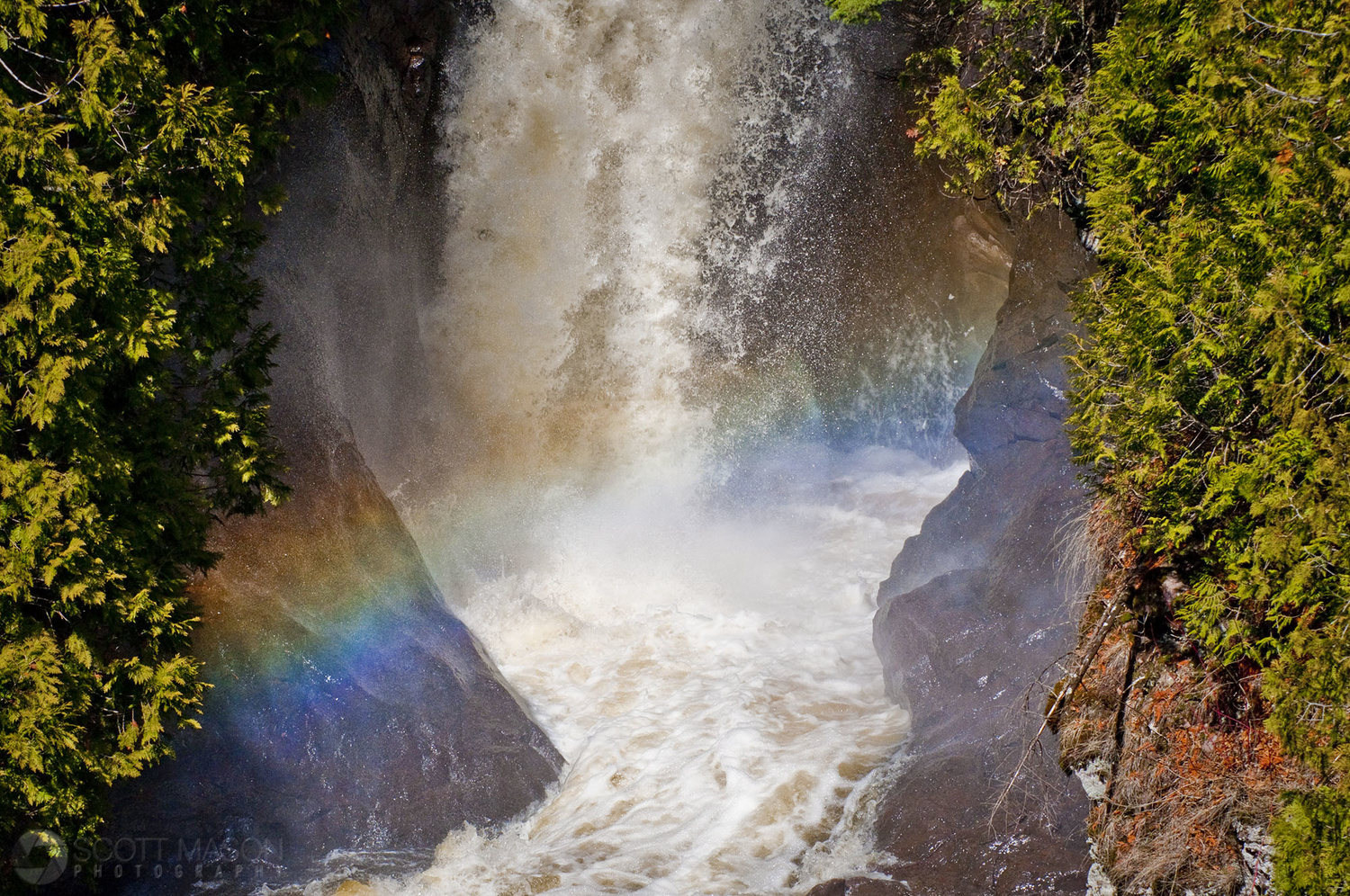 A rainbow in front of a waterfall