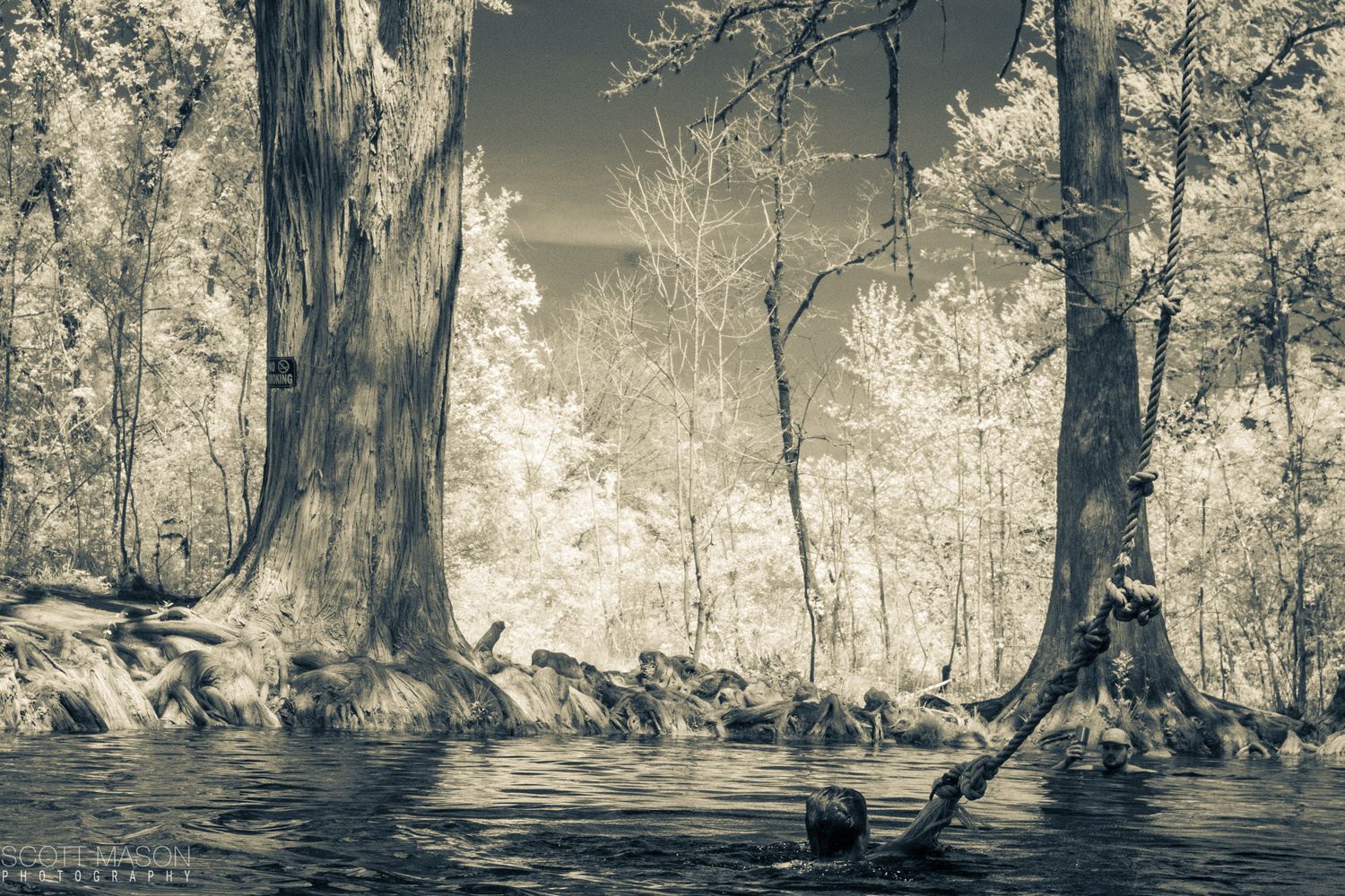 an infrared photo of a kid hanging on a rope swing in the water