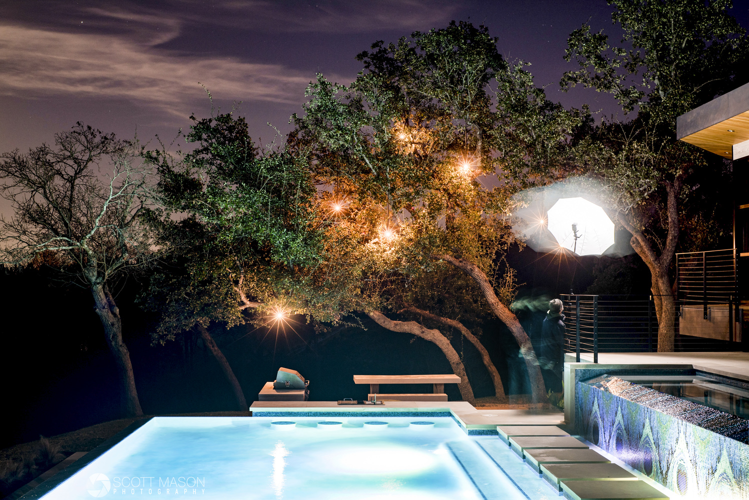 a photographer witha  strobe and umbrella lighting trees next to a pool