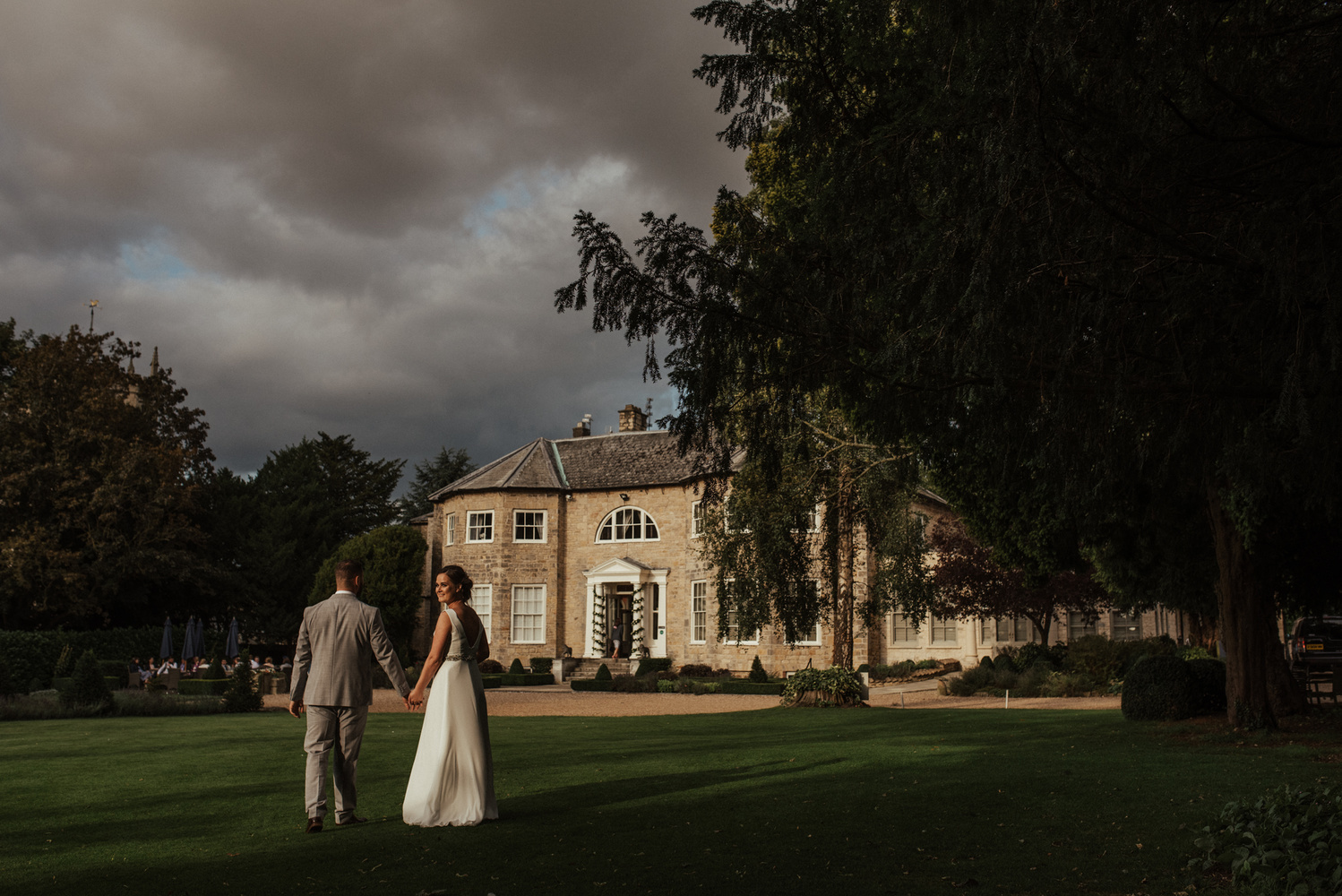A bride and groom walking in front of a manor.