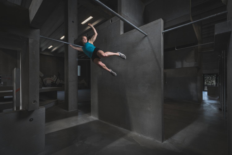 Andy Day BGI parkour photoshoot - Emilie swinging between bars