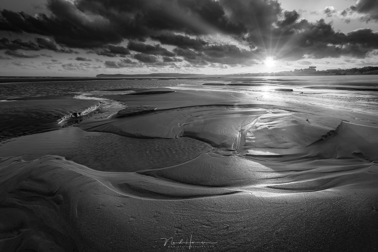 A sunrise at a beach. The sun is the brightest subject in the photo, and all attention is going to that bright spot. The patterns in the sand comes second. If black and white turns out to be very beautiful, you might consider keeping it black and white.
