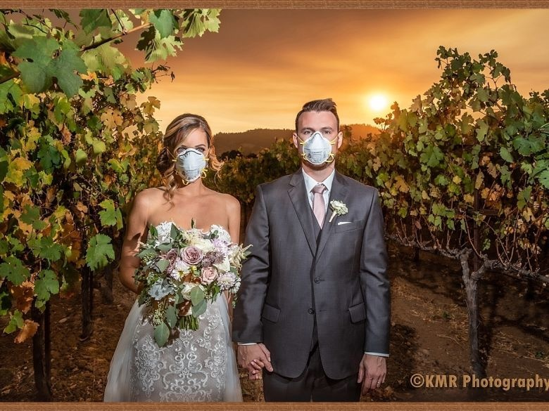 a wedding photo of a couple standing in front of the Kincade fire in California with masks on