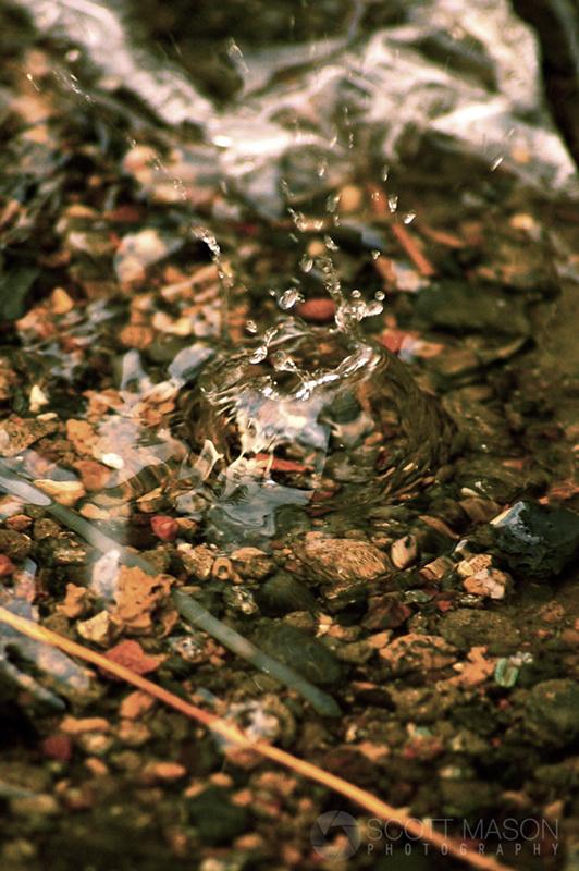 a water droplet splashing over rocks