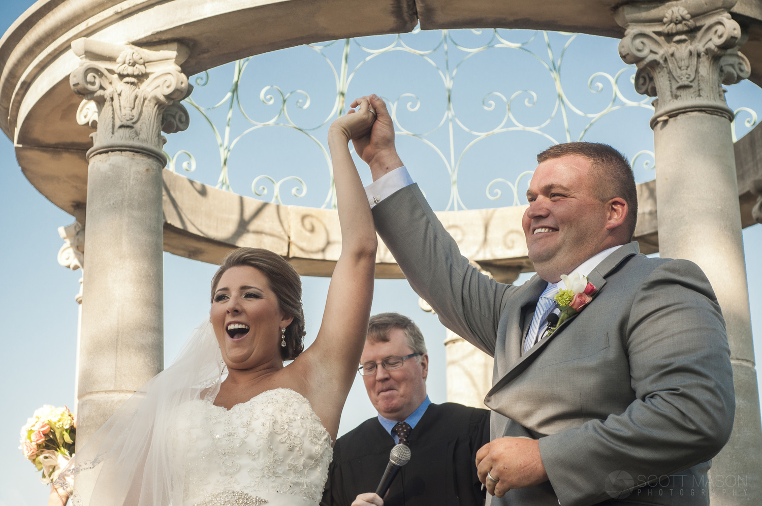 a couple at a wedding ceremony with their arms raised