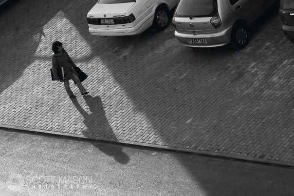 a view from above of a woman walking down a brick sidewalk