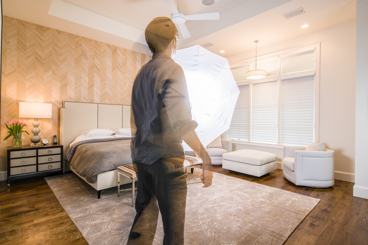 a man holding an umbrella flash inside a bedroom