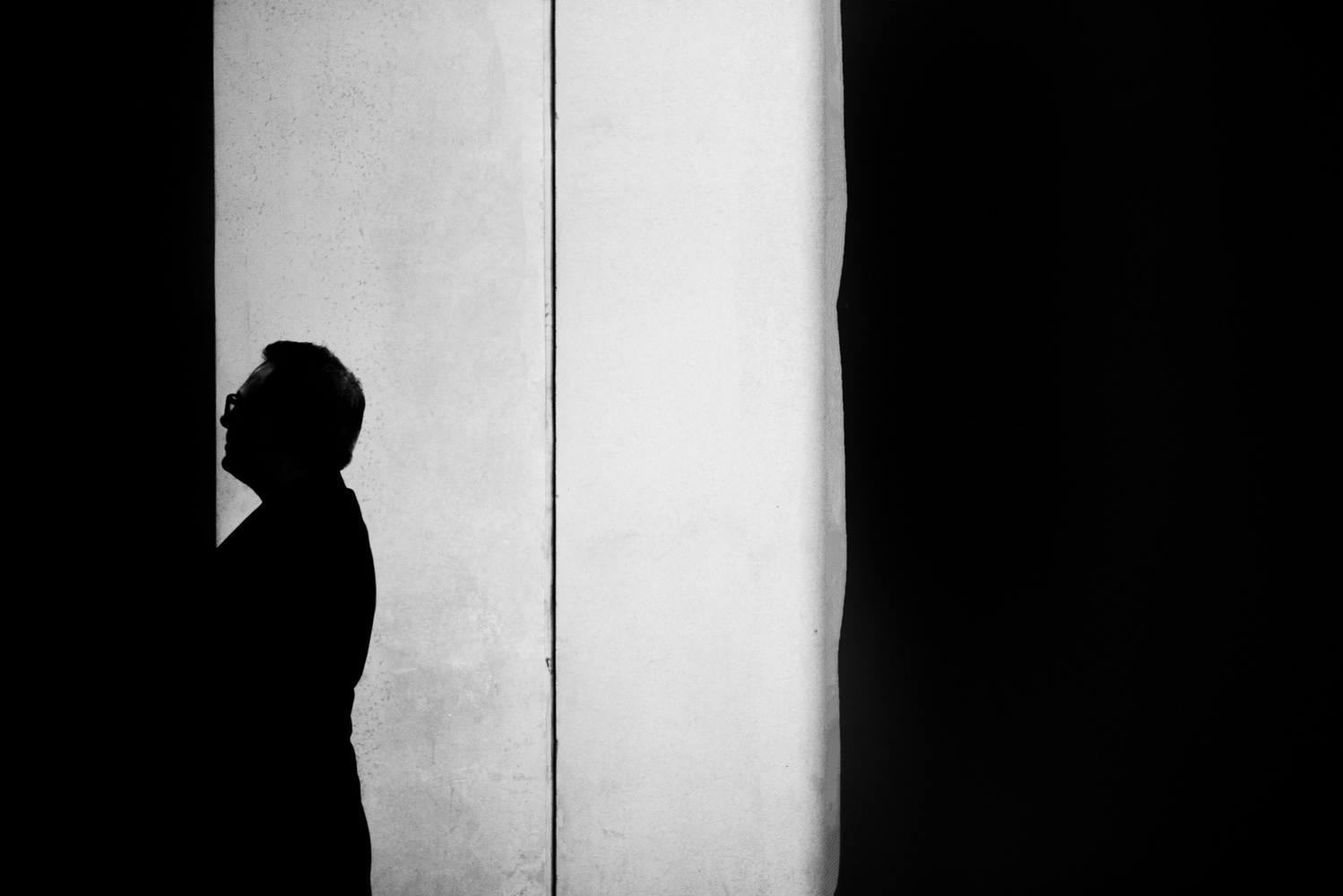 A silhouette of a man by a wall