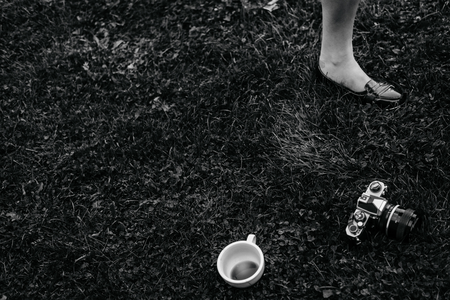Monochrome shot of a girl's shoe, tea cup and a camera