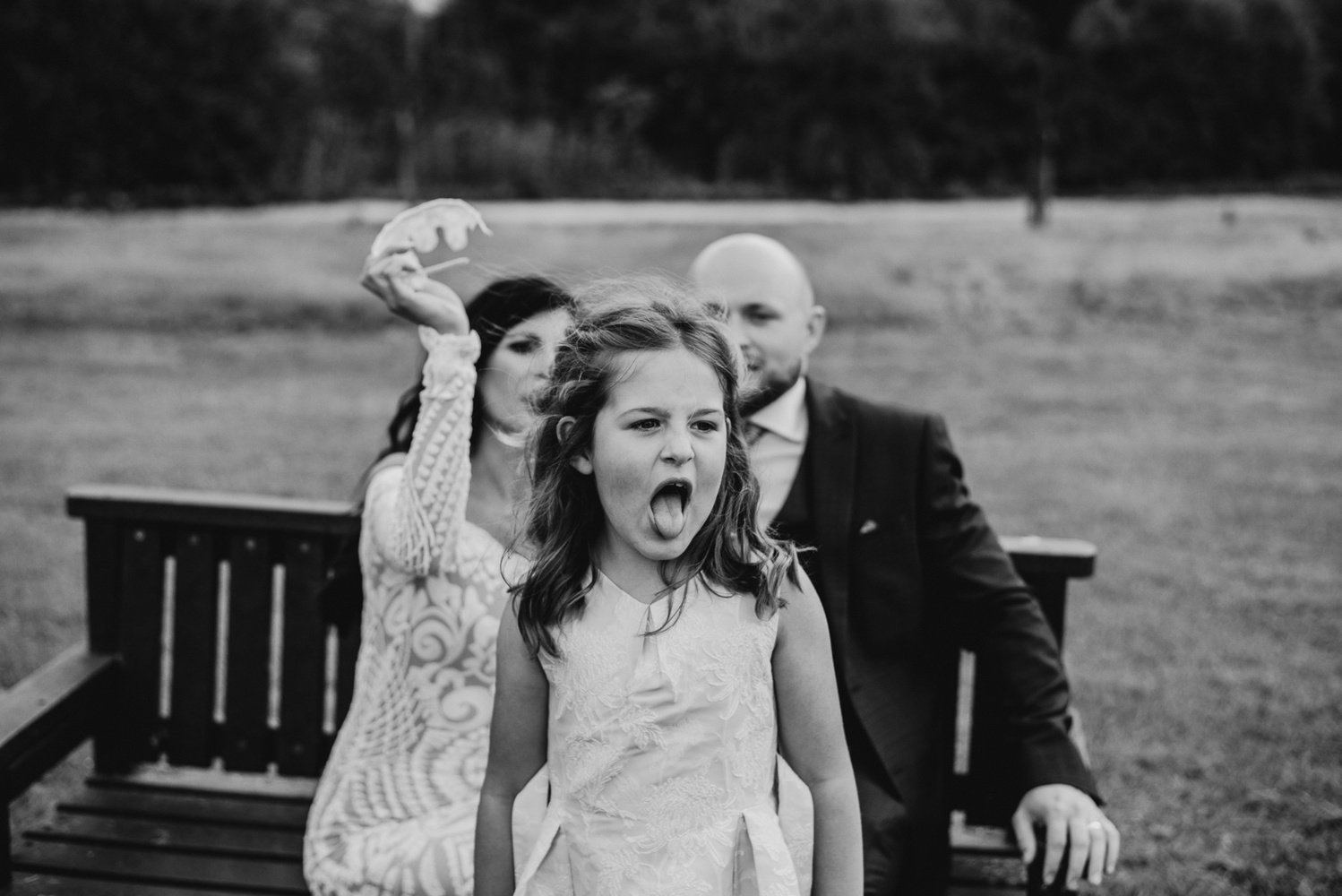 A bride, groom and their daughter in a park