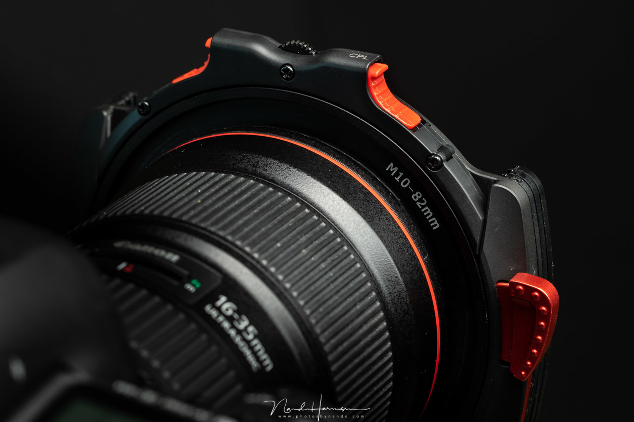 The filter holder is hold in place by a spring-loaded red lever. There is no risk of losing the filter holder with normal use. And by change it fits quite nicely with the red L-series lenses. I am sure it will also fit with the red accent of the Nikon cam