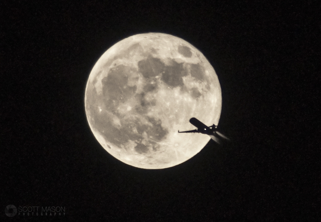 a silhouetted plane flying in front of the full moon