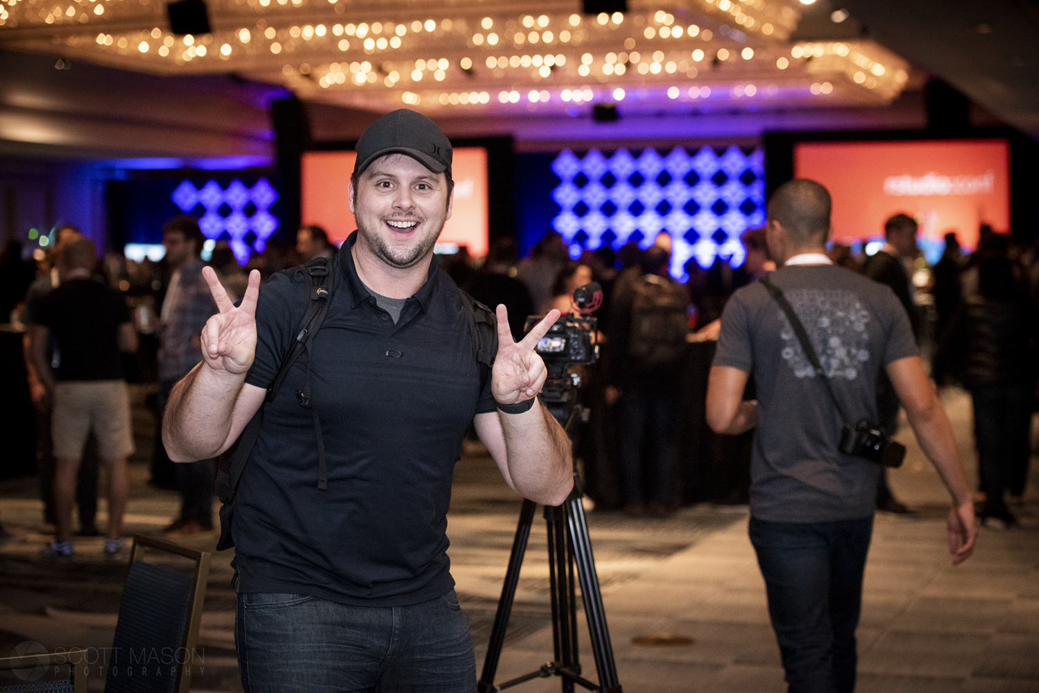 a videographer smiling and giving the peace sign at a conference