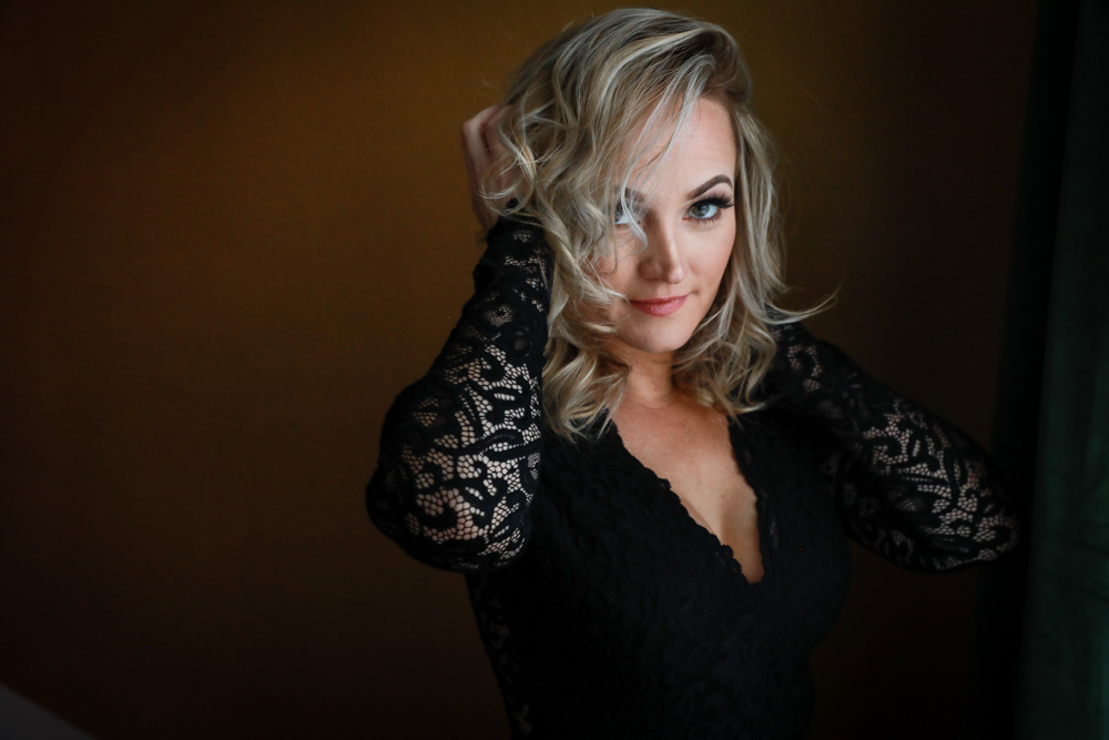 a woman with blonde hair posing in a lacey black dress