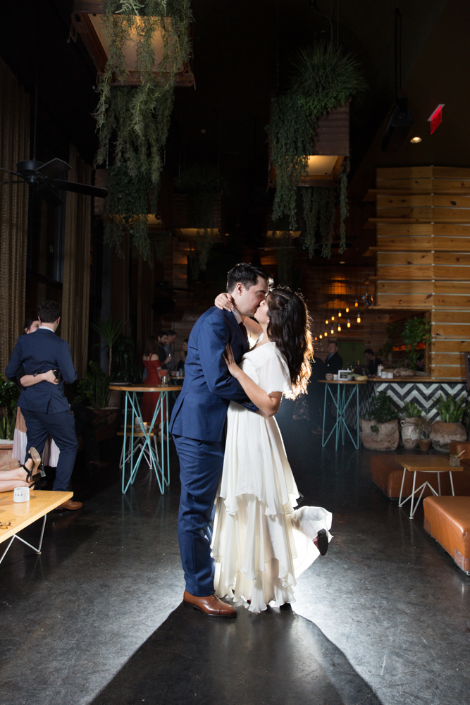 newlyweds kissing inside a venue with backlighting