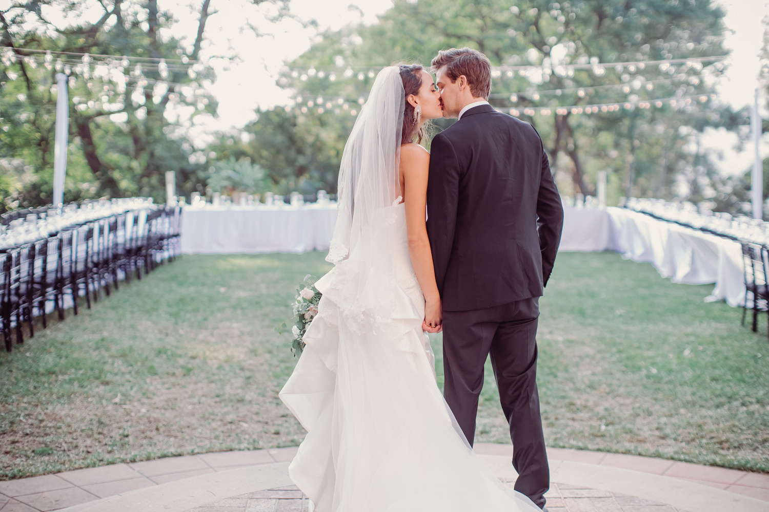 a wedding couple stands kissing in front of empty seats.