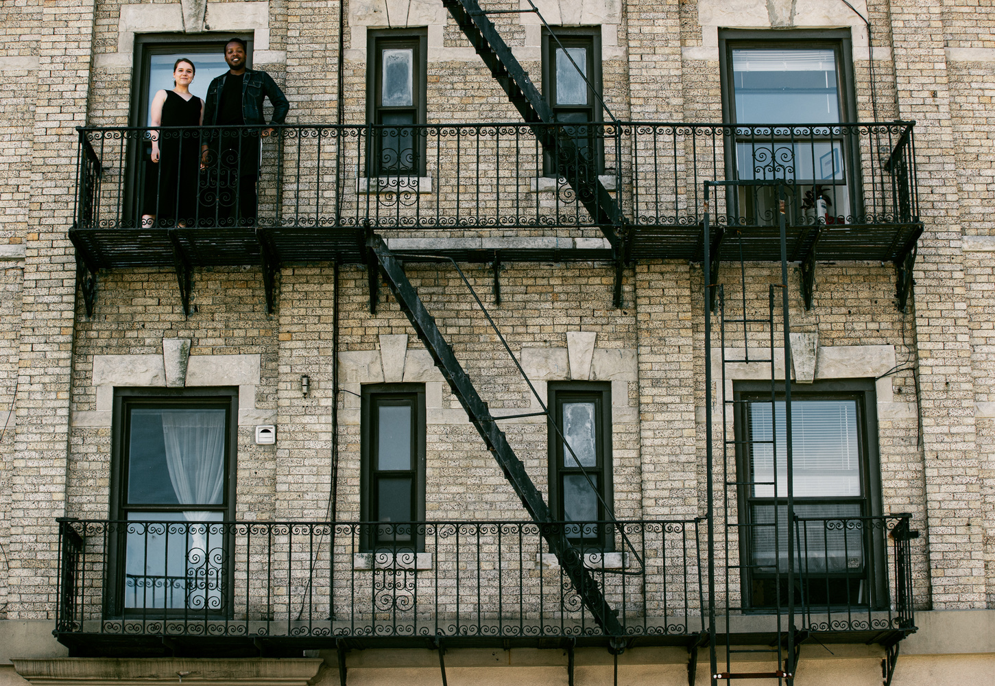 A couple stand on their Brooklyn fire escape for a portrait for the Come To My Window project