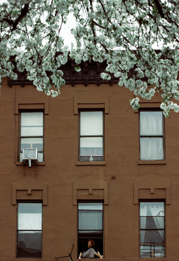 A young woman sits on her Brooklyn window sill for the Come To My Window project
