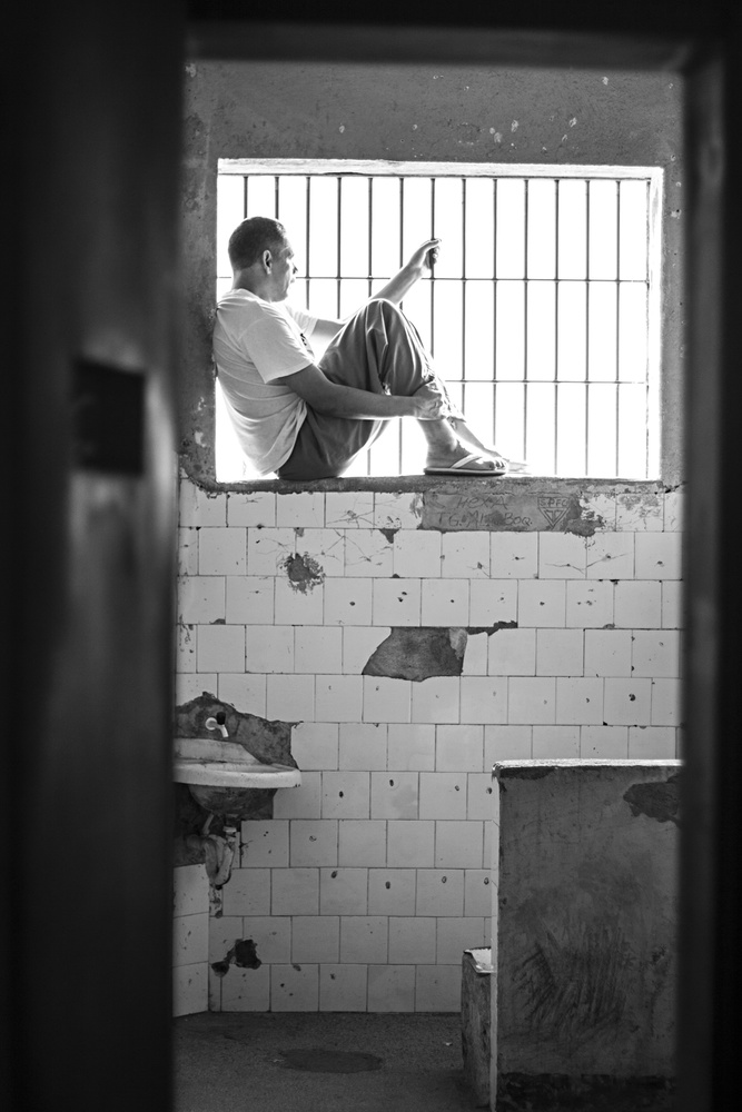 A male inmate inside his prison cell.