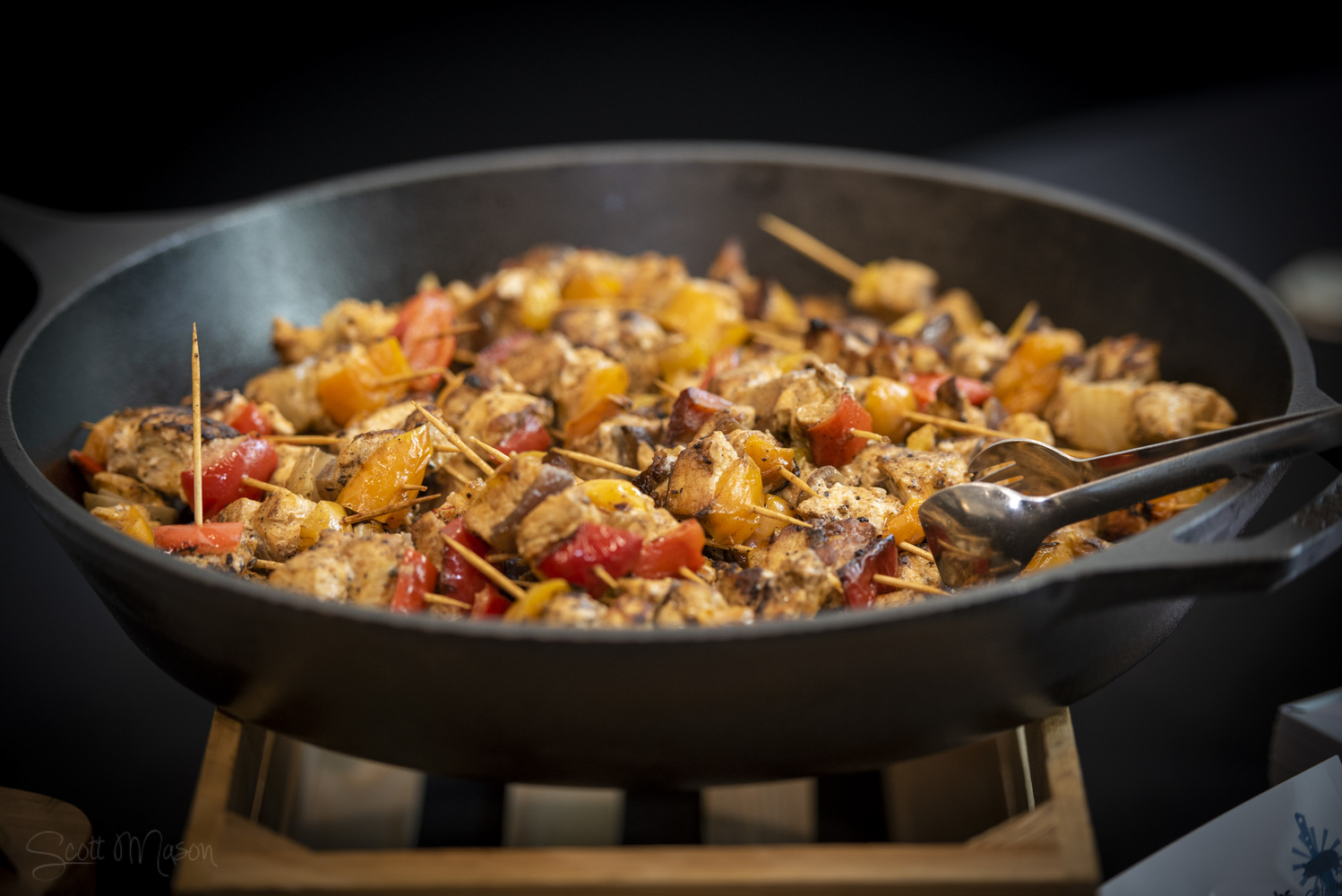 a cast iron skillet with kebabs cooking on it