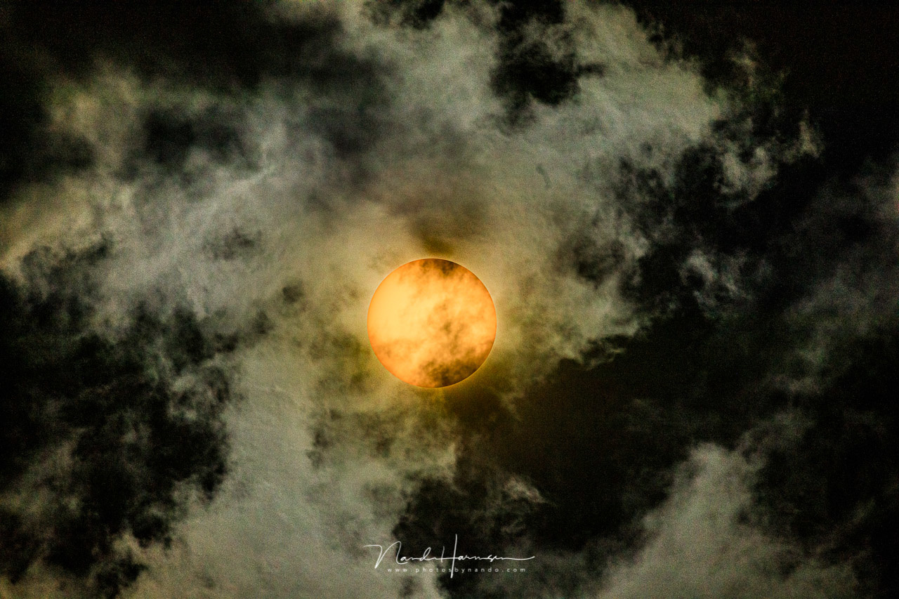 The sun behind clouds. The black parts are in white fluffy clouds in reality, which turned completely black by the filter. It gives an idea how bright the sun and white parts are, and how much light the filter holds (Canon EOS 5D4 + EF100-400mm @ 400mm +