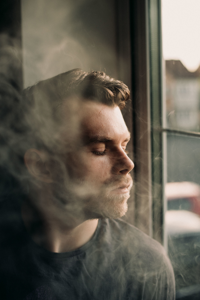 Seorang pria duduk di dekat jendela.